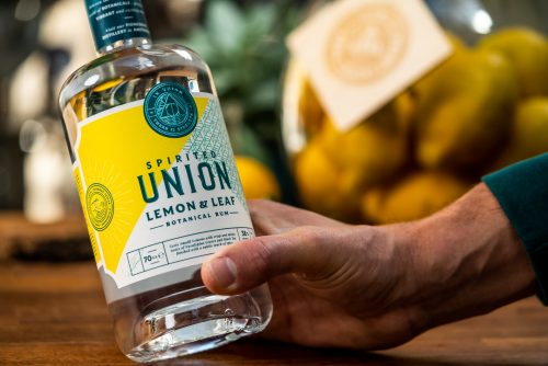 Lemon & Leaf Botanical Rum bottle in hand